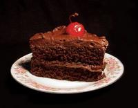 Chocolate Cake On Plate With Frosting And Cherry.jpg